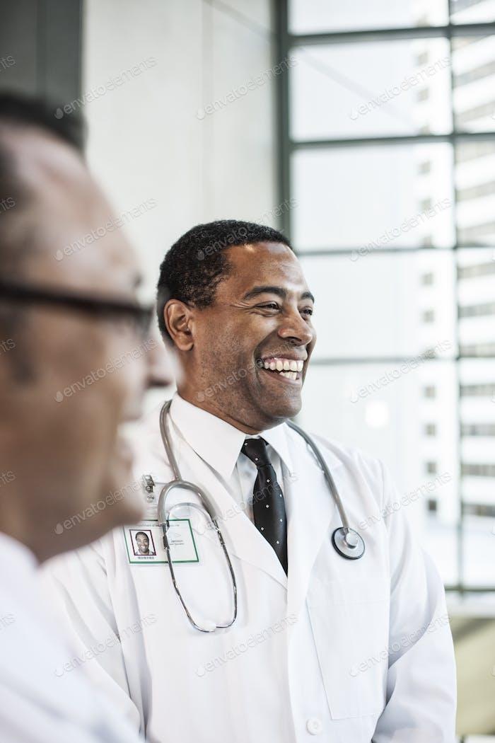 Schwarzer Arzt im Labormantel mit einem Stetheskop.