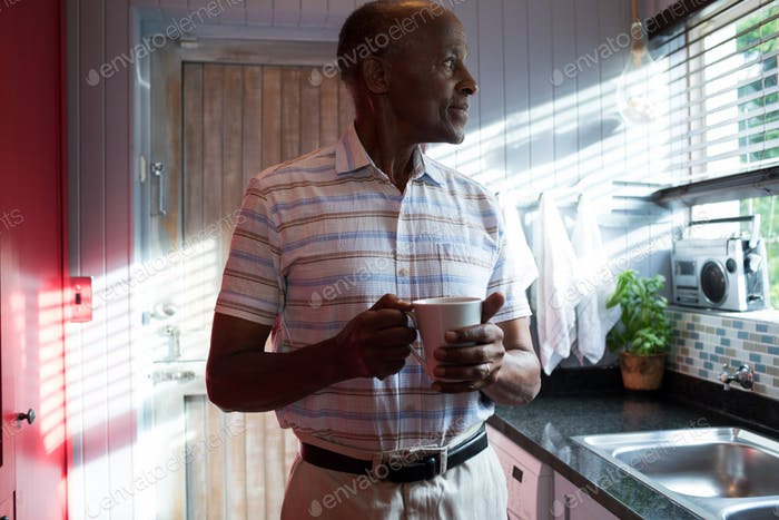Thoughtful man with coffee cup at home