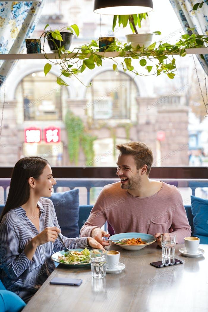 Attraktives junges Paar mit Mittagessen im Café drinnen