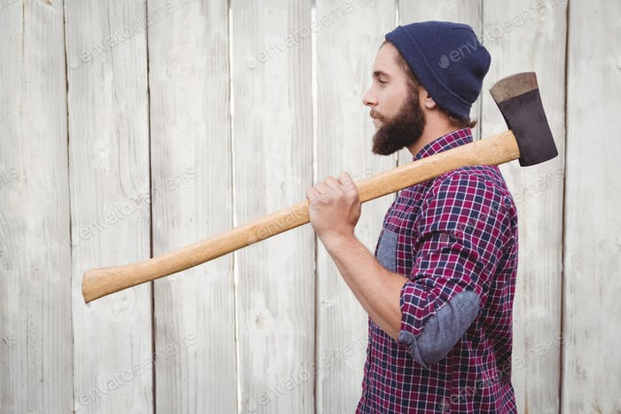 Seitenansicht des Hipsters mit Axt auf Schulter gegen Holzzaun