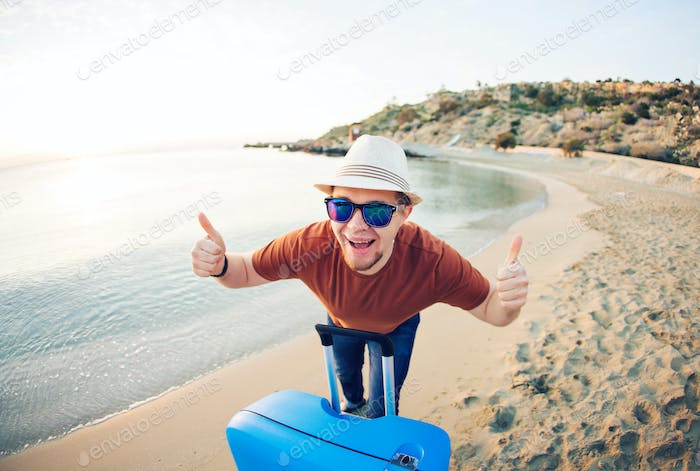 Funny man with suitcase showing thumbs up against the blue ocean. Travel concept.