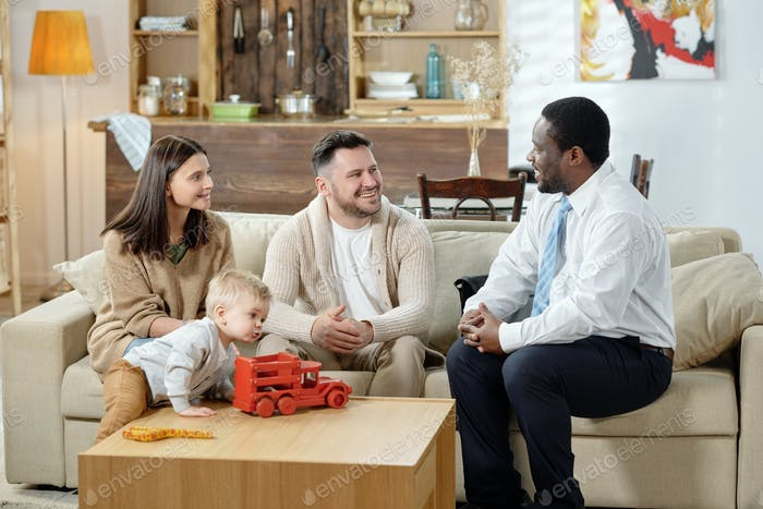Cheerful counselor and family gathering on couch