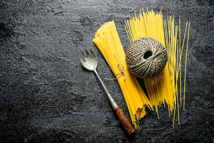 Dry spaghetti with twine and ladle.