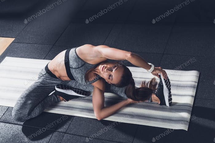 young sportive woman stretching on mat before training in gym