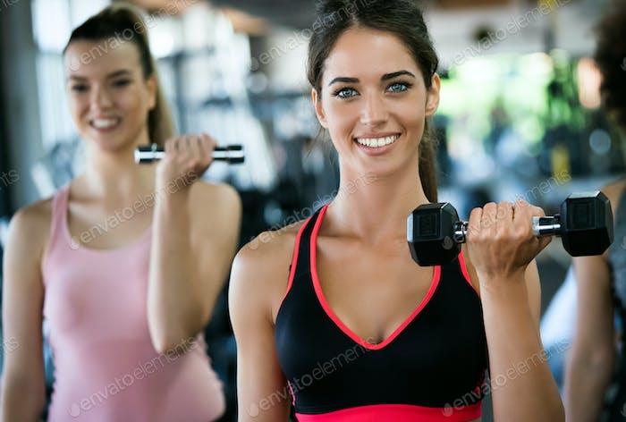 Fitness, Sport, Training, Gym und Lifestyle-Konzept. Gruppe von Frauen, die im Fitnessstudio trainieren