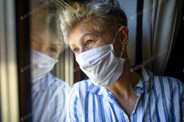 Senior woman with face mask indoors at home, corona virus and quarantine concept