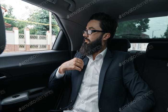 Confident businessman sitting on the car back sit while thinking