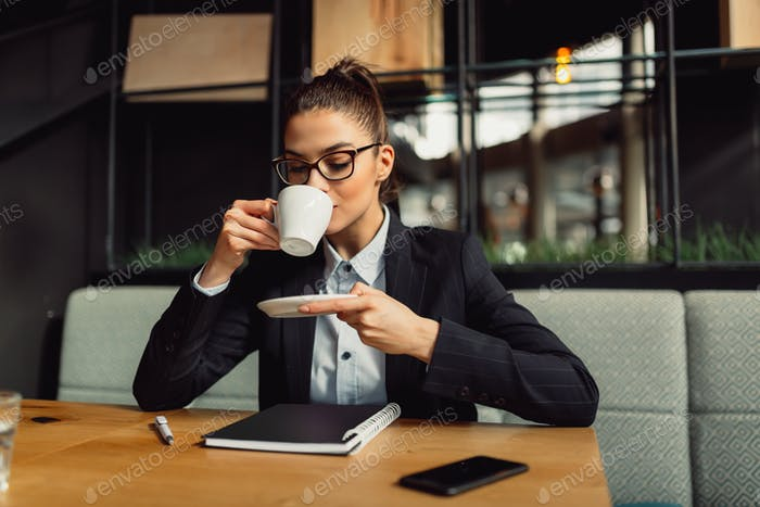 Pretty businesswoman drinking coffee at coffee shop.