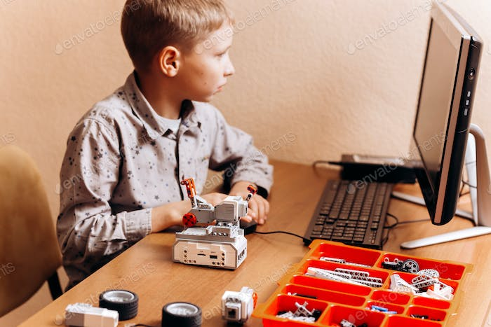 Smart boy dressed in gray shirt makes a robot from the robotic constructor at the desk with computer