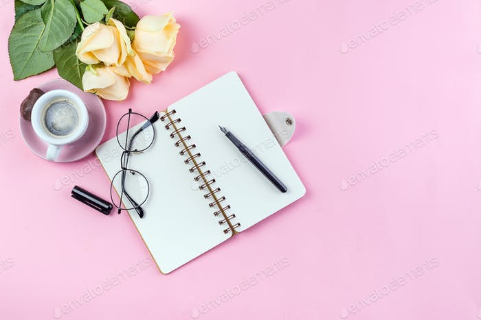 Morning coffee mug with glasses, empty notebook, pencil and rose on pink table top view . Woman
