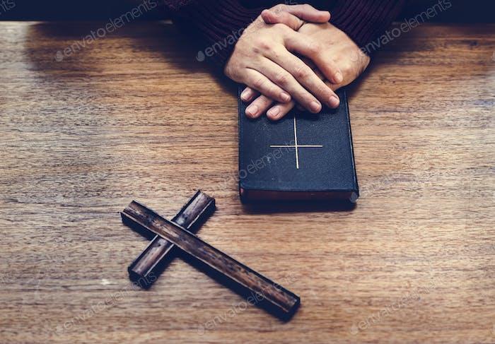 Hände über Bibel auf Holztisch