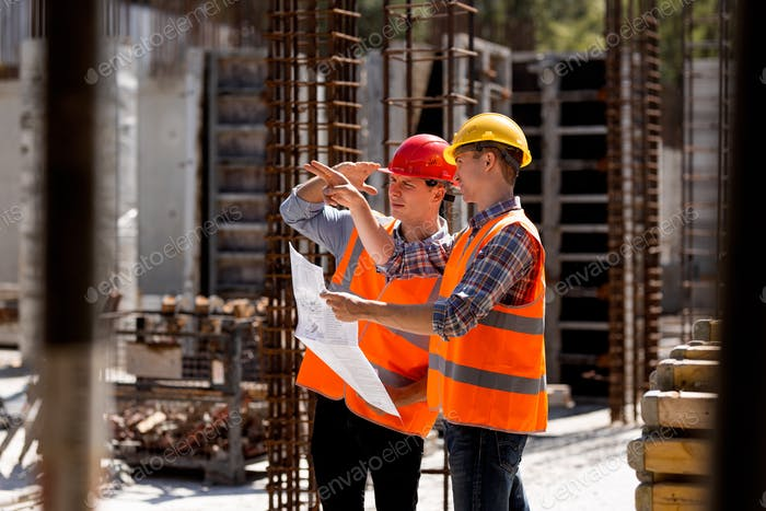 Structural engineer and construction manager in orange work vests and hard helmets explore