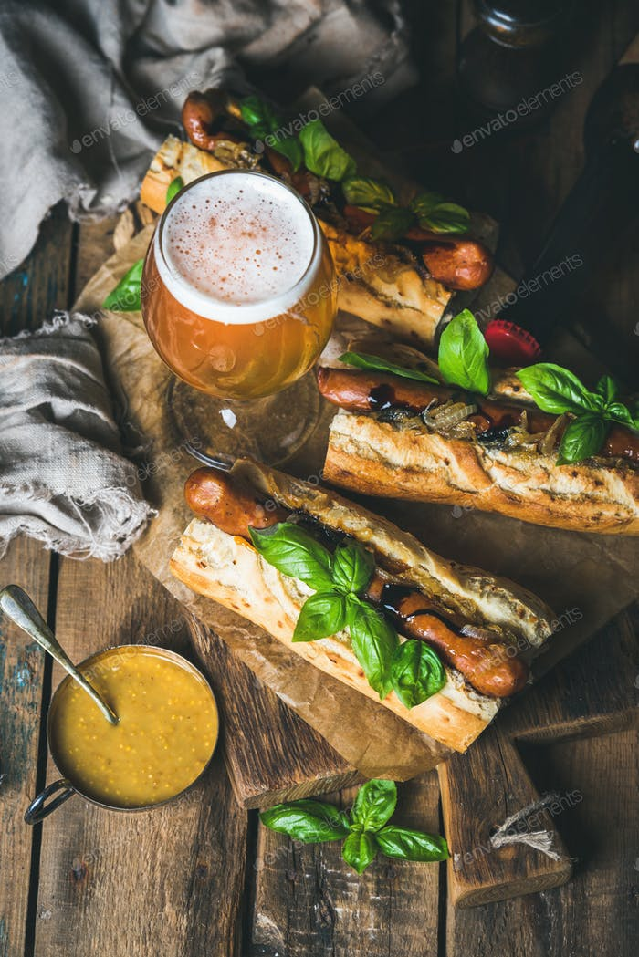 Glass and bottle of unfiltered beer, grilled sausage dogs