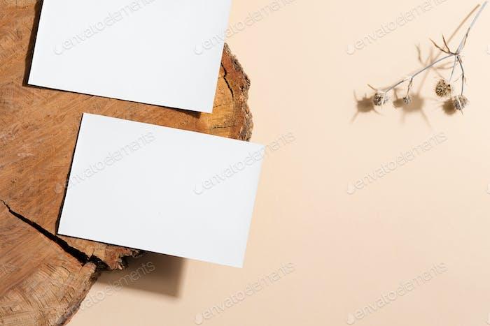 Пустая белая бумажная открытка на старом деревянном столе и бежевом фоне с цветком