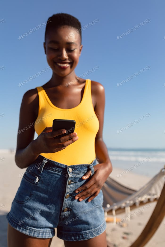 Happy African-american woman using mobile phone with her thumbs in belt loops on the beach