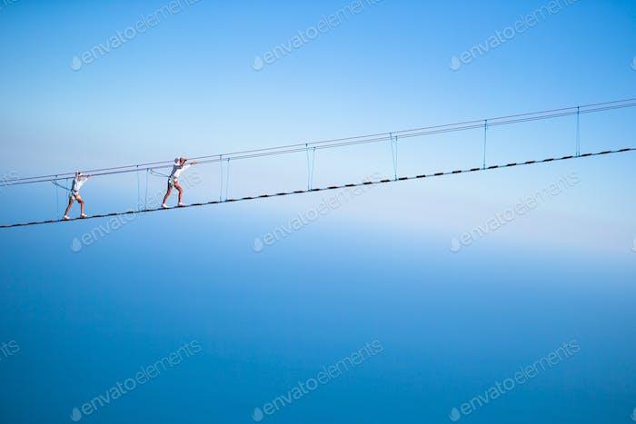 Girls crossing the chasm on the rope bridge. Black sea background, Crimea, Russia