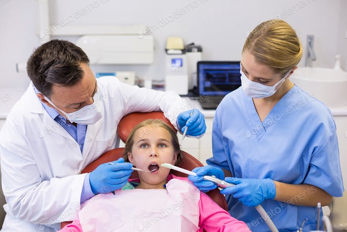 Dentist and nurse examining a young patient with tools