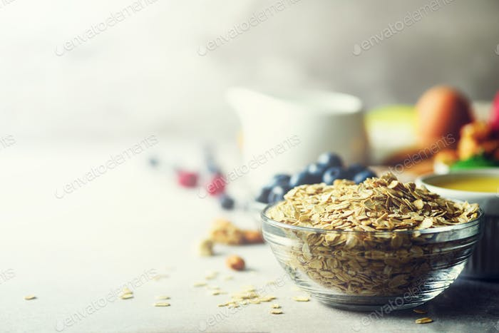 Organic ingredients for healthy breakfast - berries, milk, egg, oatmeal on grey concrete background