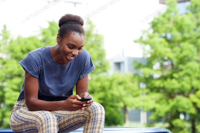 Happy young woman looking at mobile phone outdoors