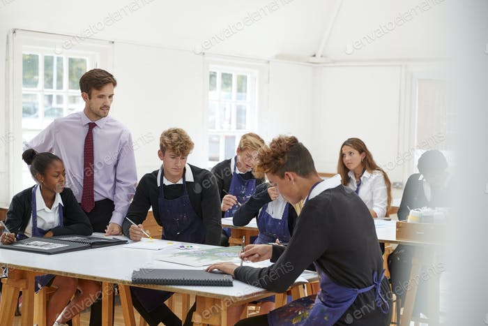 Teenage Students Listening To Teacher In Art Class