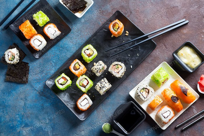 Traditional Japanese food- sushi, rolls, chopsticks, soy sauce on color stone background. Sushi menu