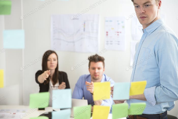 Businessman Looking At Adhesive Notes While Colleagues Pointing