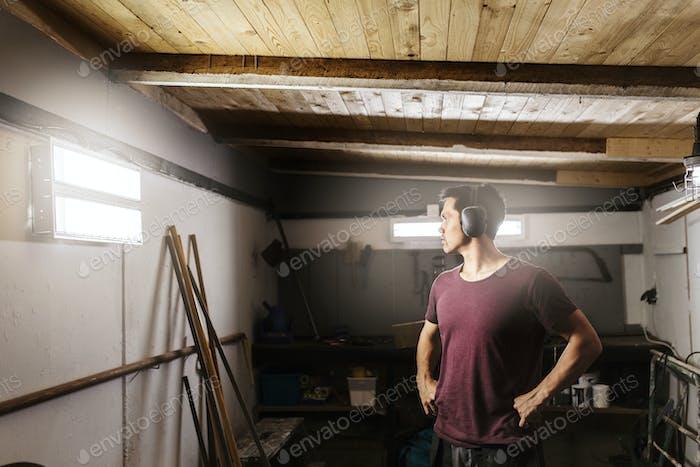 Man wearing ear muffs in garage