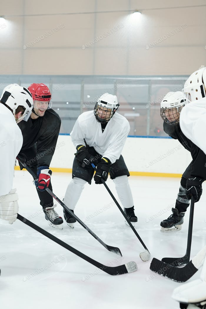 Group of professional hockey players in skates standing in circle on ice rink