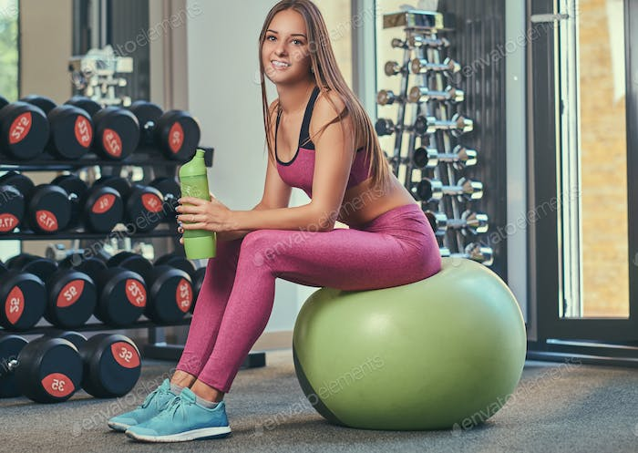 Fit girl in pink sportswear sitting on a fitness ball with a bottle of water at a gym.