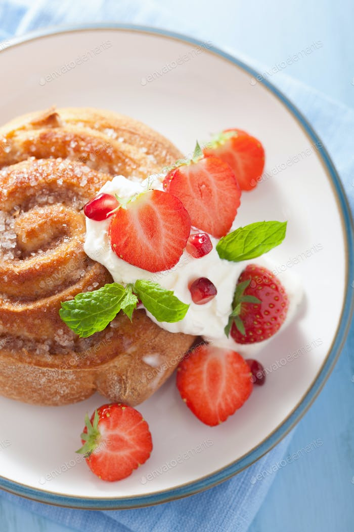 sweet cinnamon roll with cream and strawberry for breakfast