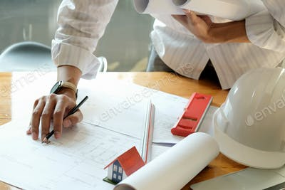 Designers are designing houses. Model houses and house plans on