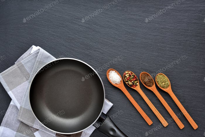 Empty frying pan with napkin and spices on dark grey stone backg