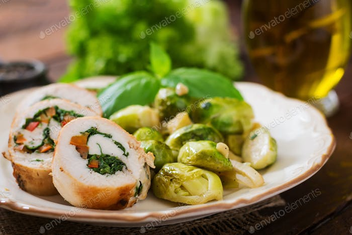 Chicken rolls with greens, garnished with stewed Brussels sprouts, apples and leeks on plate.