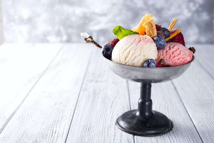 Bowl with ice cream with three different scoops of white, yellow, red colors and waffle cone