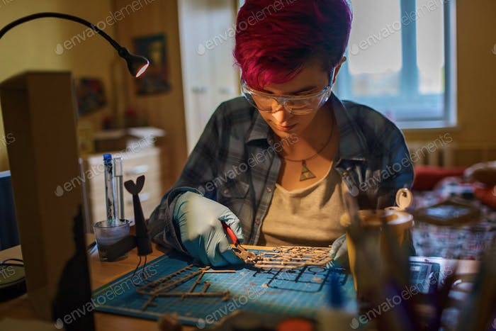 Geek teenage girl engineering an airplane model at home, generation Z lifestyle, nerd subculture
