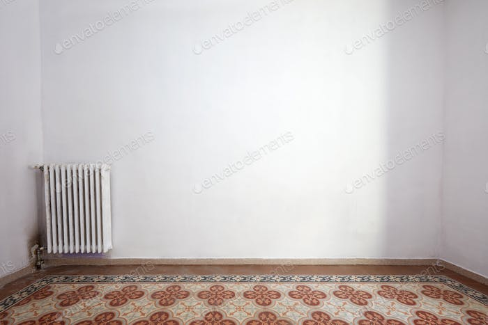 Empty room interior with tiled floor and white wall
