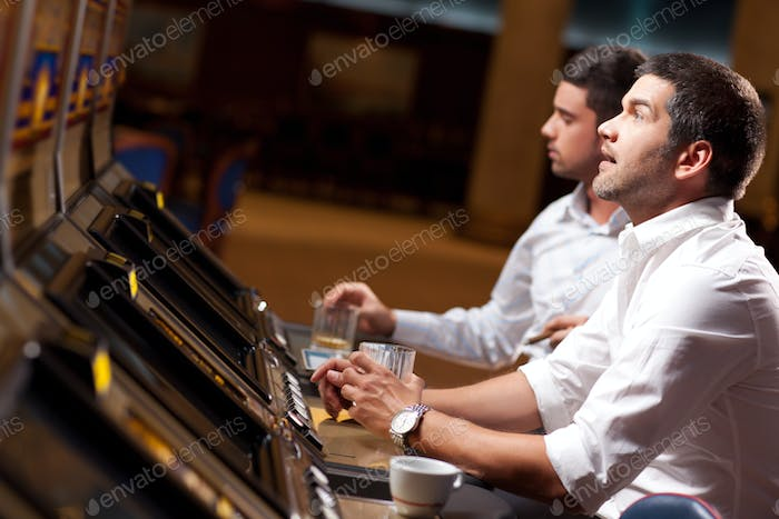 handsome men playing the slot machine