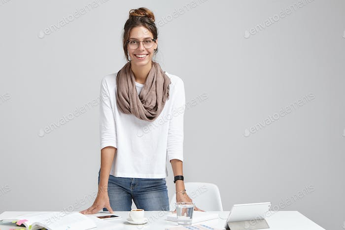 Picture of successful female model wears formal clothes, stands at work place, studies graphs, has h