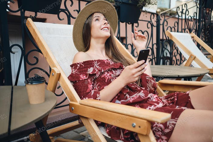 Young smiling girl in dress and straw hat holding cellphone happily looking up sitting on deck chair