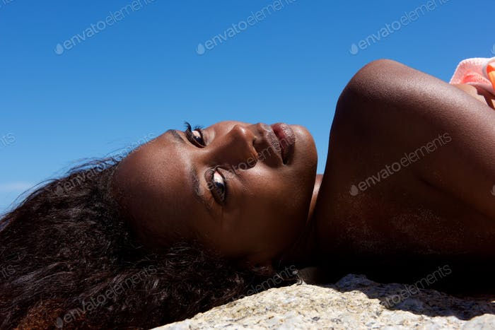 Beautiful young african woman lying outdoors