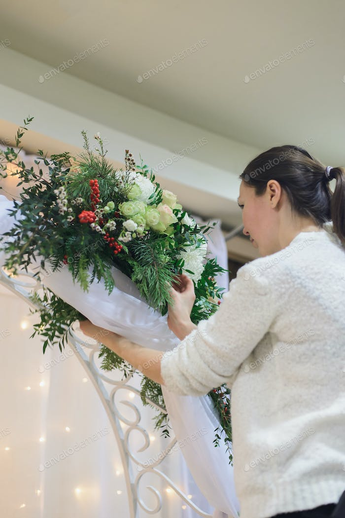 florist make winter wedding floral arch composition indoors