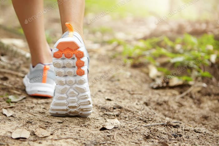 People and sports. Athletic pair of female legs in running shoes on trail. Young attractive woman jo