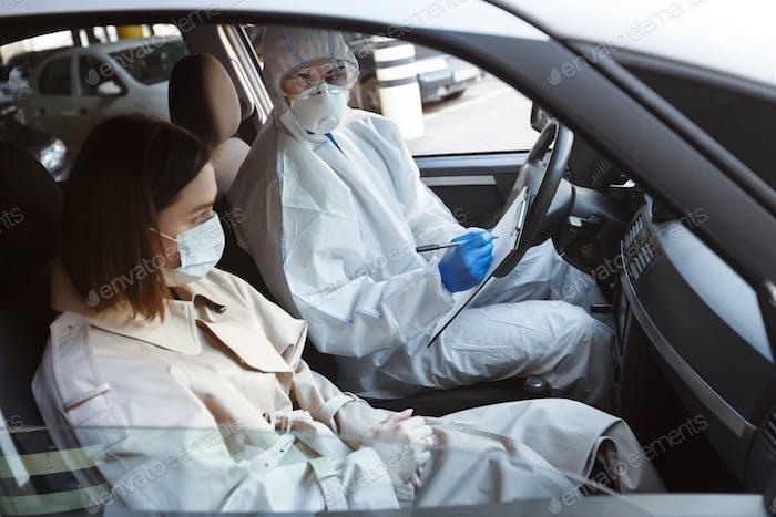 Doctor in virus protective suit interrogating woman patient