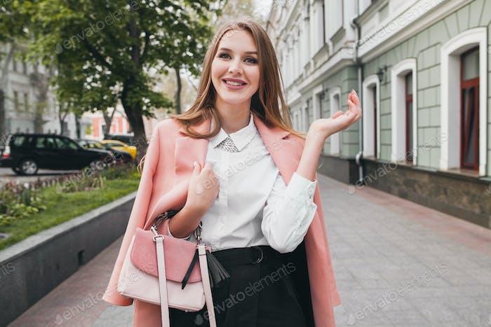 lindo atractivo y elegante sonriente mujer caminando calle de la ciudad en abrigo rosa