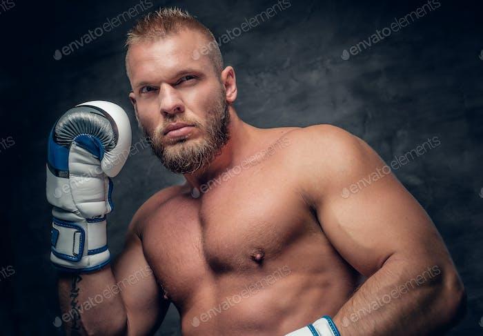 Brutal puncher in a boxer gloves over grey vignette background.