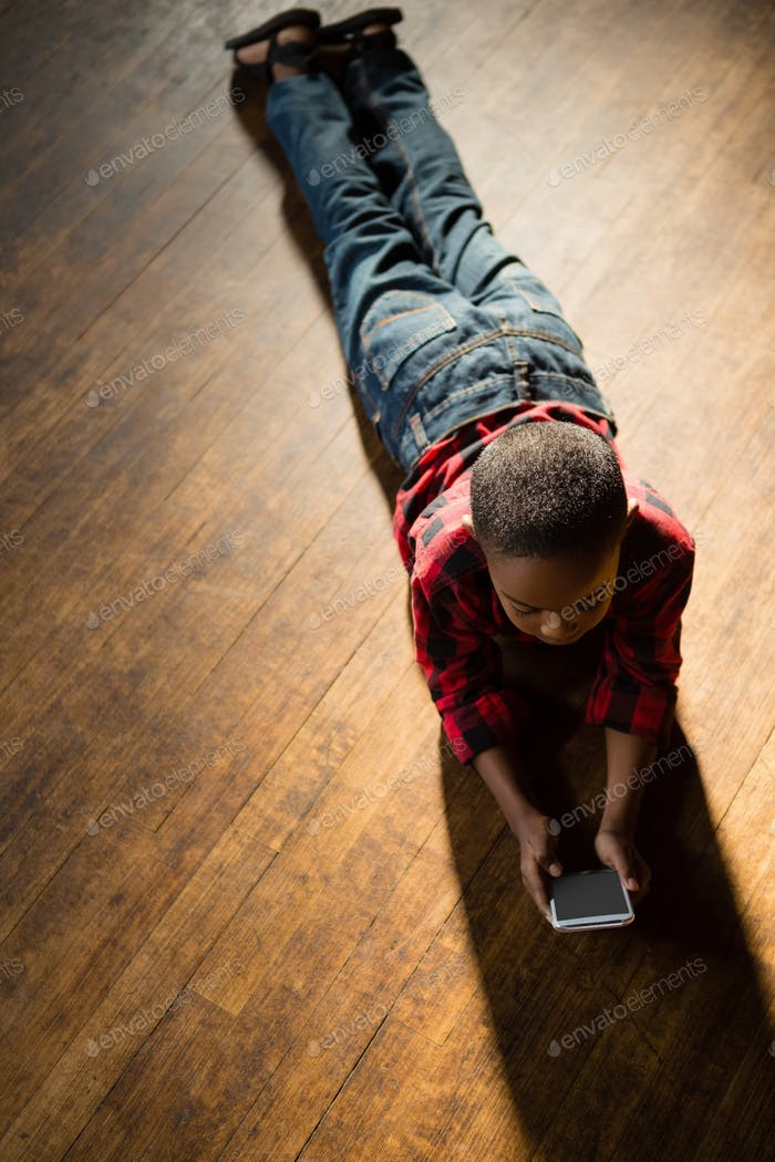 Boy lying on wooden floor using mobile phone