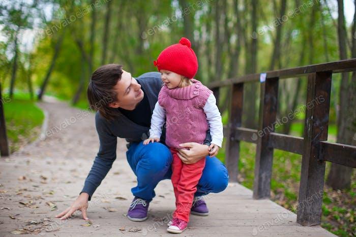 Porträt von Junger Vater zu Fuß mit seiner niedlichen Tochter im Herbst Park