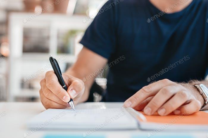 Hände eines jungen Mannes schreiben in einem Bürotagebuch