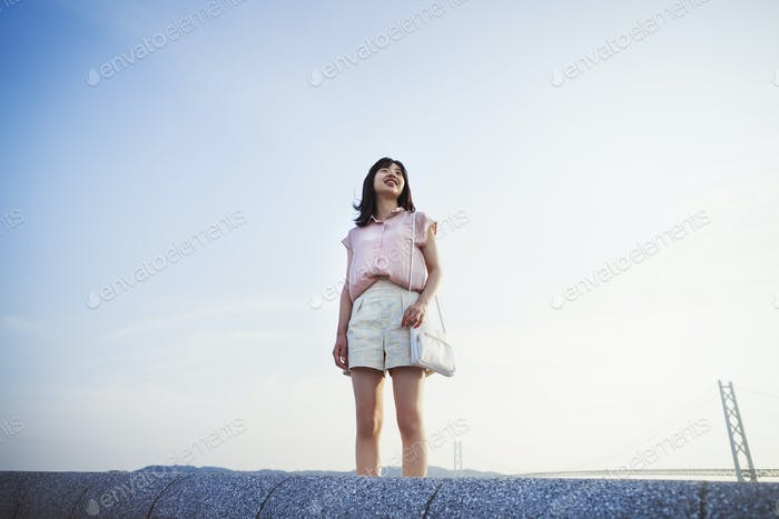 Young woman in shorts and pink shirt standing alone in open space, with a large suspension bridge in