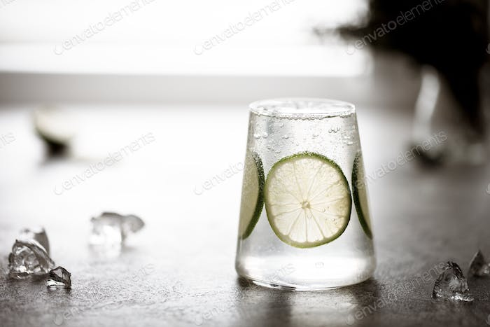 glass of fresh drinking water and a lime. or Alcoholic Gin and Tonic